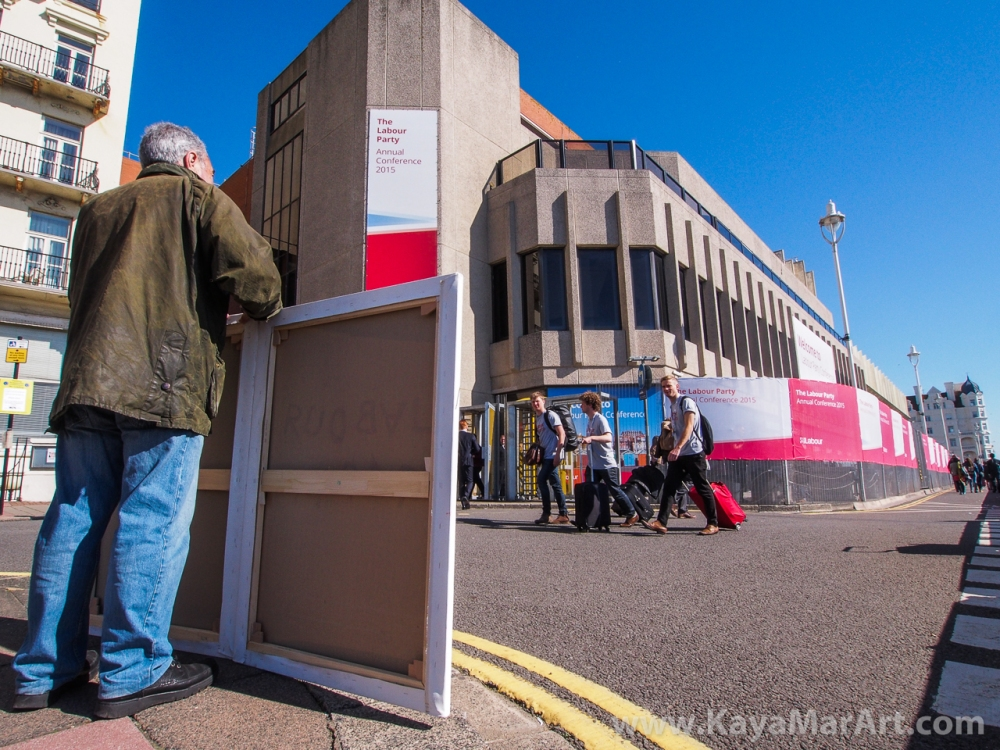 Kaya Mar is impossible to ignore as he stands outside the Brighton Conference Centre during the Labour Party Conference with three large satirical paintings.